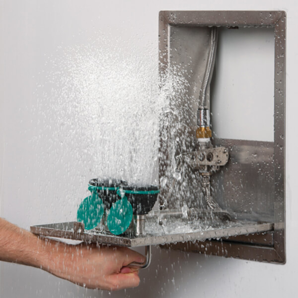Eye wash station attached to the wall with water coming out of the eye flushing nozzles.