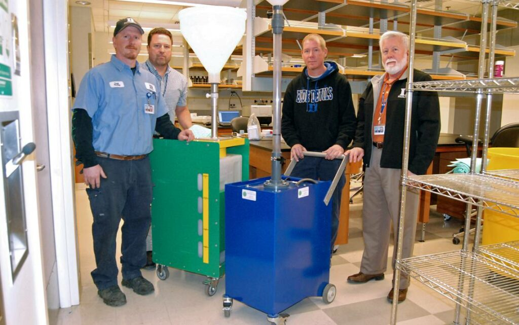 4 men standing around a blue square metal container with a handle and wheels.