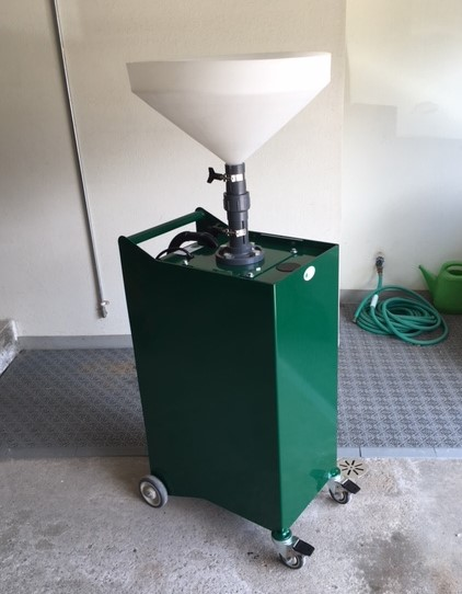 Green square metal container on wheels with a giant funnel on top.