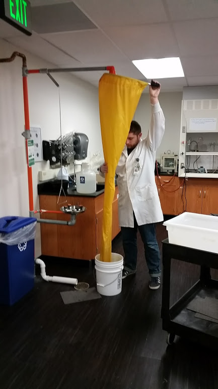 Man on tip-toes holding up a ring with a yellow shower curtain attached. There is a bucket under the curtain to catch water.
