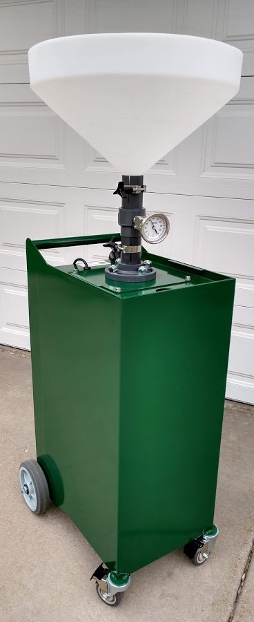 Square green metal container on wheels with a giant funnel on top.